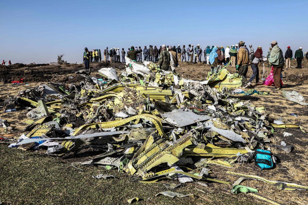 People stand near collected debris at the crash site of Ethiopia Airlines near Bishoftu, a town some 60 kilometres southeast of Addis Ababa, Ethiopia. AFP