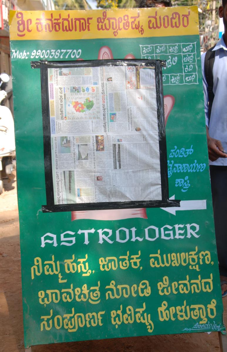 The board in front of an astrologer's shop that has been covered by election officials in Mandya. DH Photo