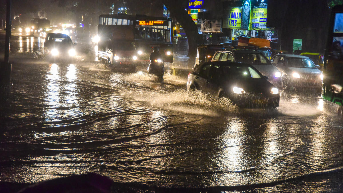 Vehicles struggle to navigate a flooded JC Road after sudden showers lashed the city on Friday evening. DH PHOTO