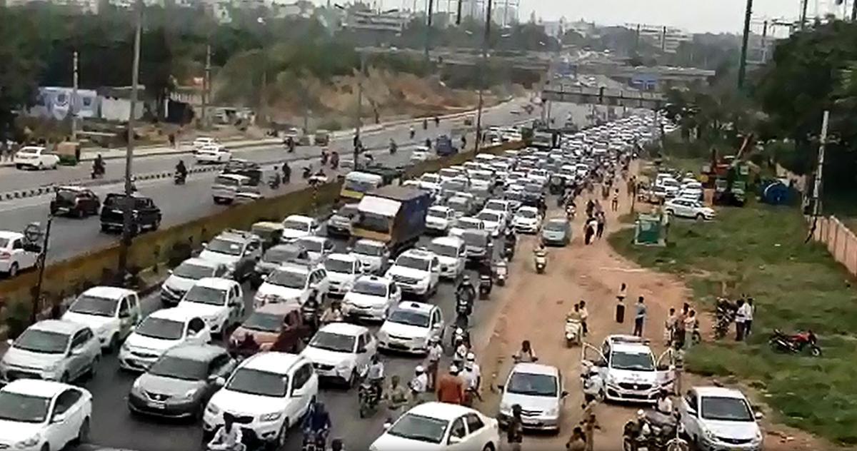 Airport-bound vehicles are stuck in the jam near the Sadahalli Gate on Ballari Road on Monday. VIDEO GRAB