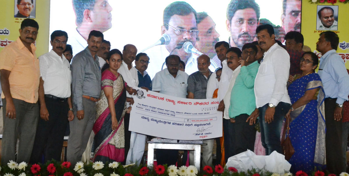 Members of State Government Employees' Association hand over a cheque for Rs 100 crore to Chief Minister H D Kumaraswamy towards Chief Minister's Relief Fund at Jambur in Somwarpet taluk on Friday.