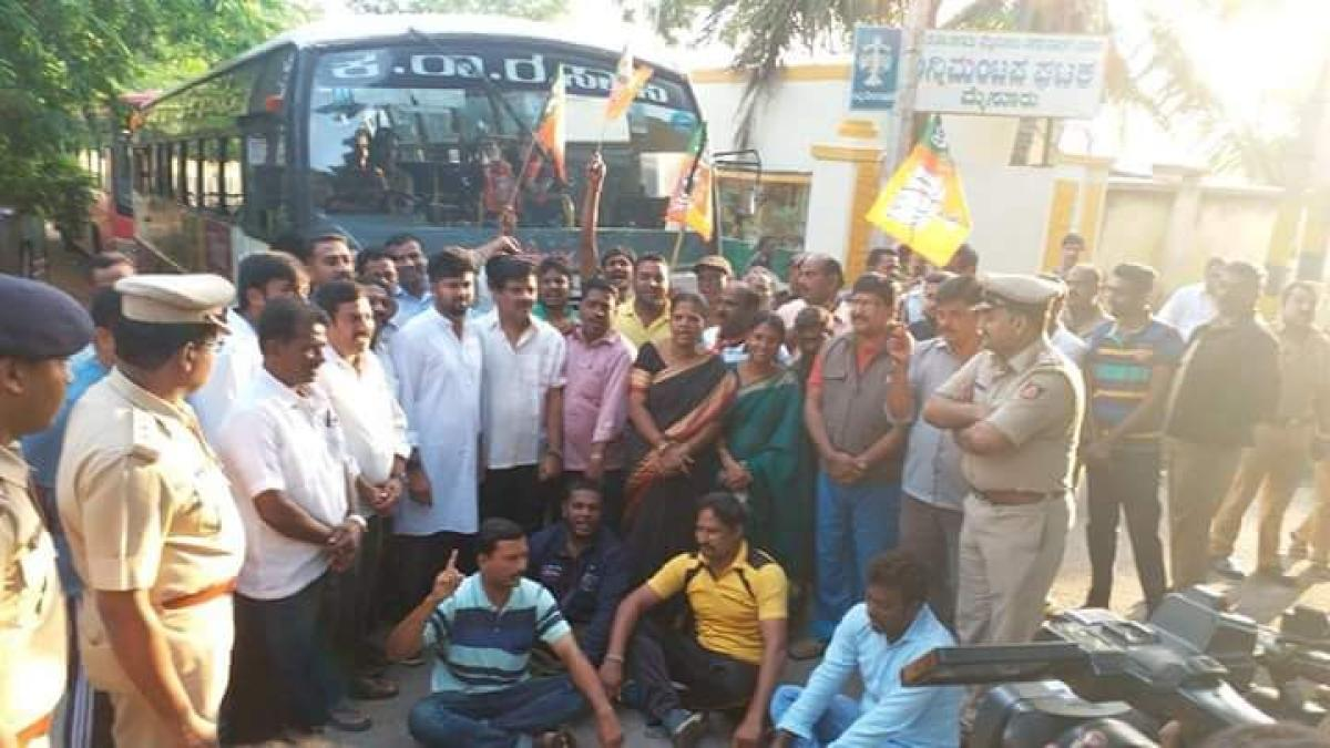 MP Pratap Simha, MLA L Nagendra and other BJP workers blocking KSRTC bus services in Mysuru on Monday. (DH Photo)