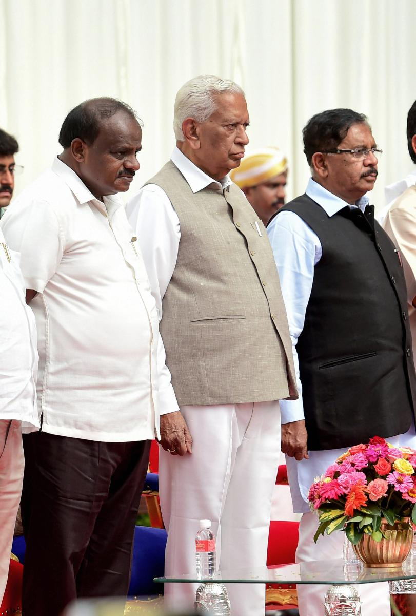 Karnataka Governor Vajubhai Vala and Chief Minister H D Kumaraswamy and Deputy Chief Minister G Parameshwara during the swearing-in ceremony of the new government.