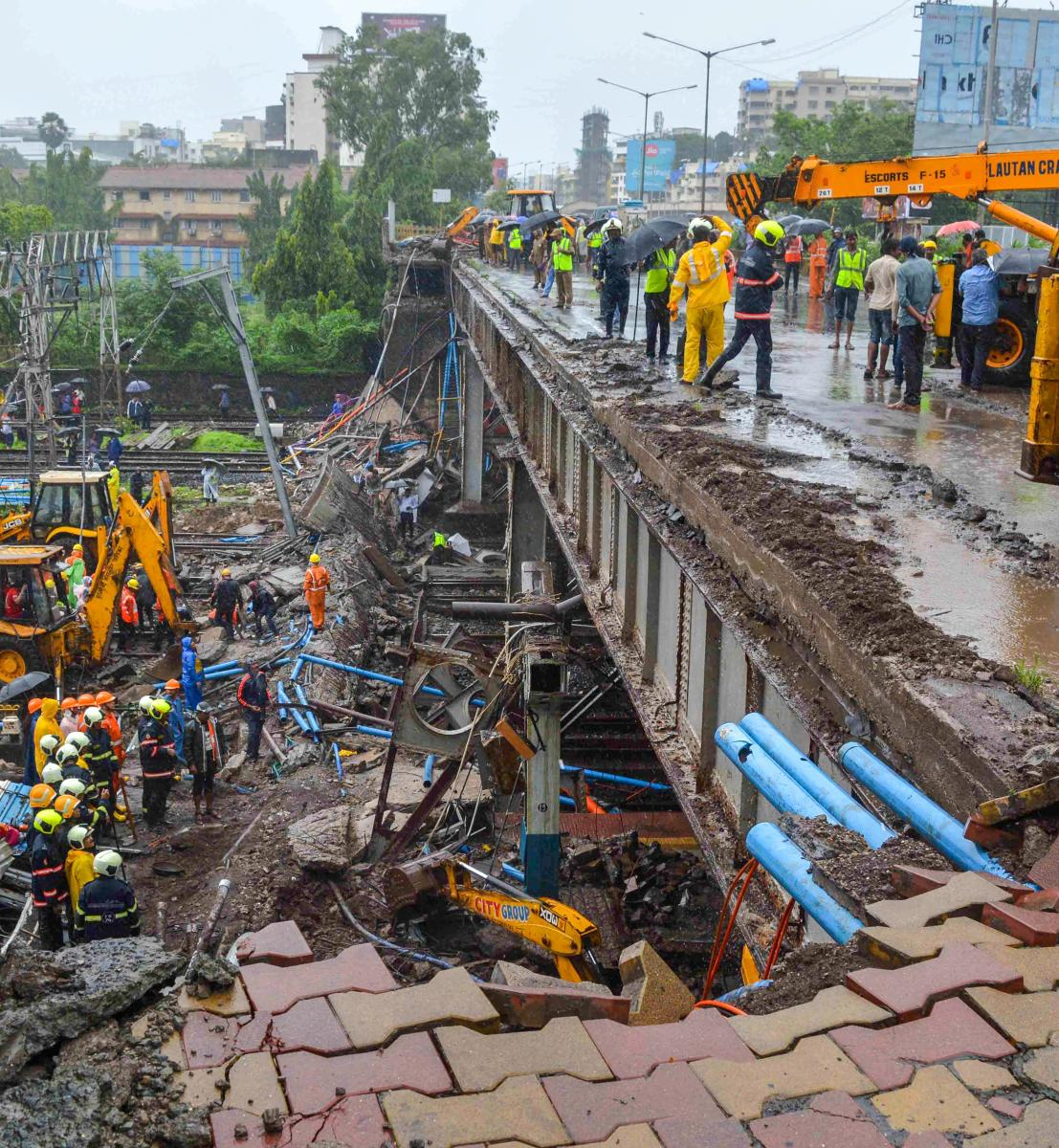 Rescue and relief work underway after a foot overbridge collapsed on the railway tracks following heavy rains, at Andheri Station in Mumbai. PTI photo