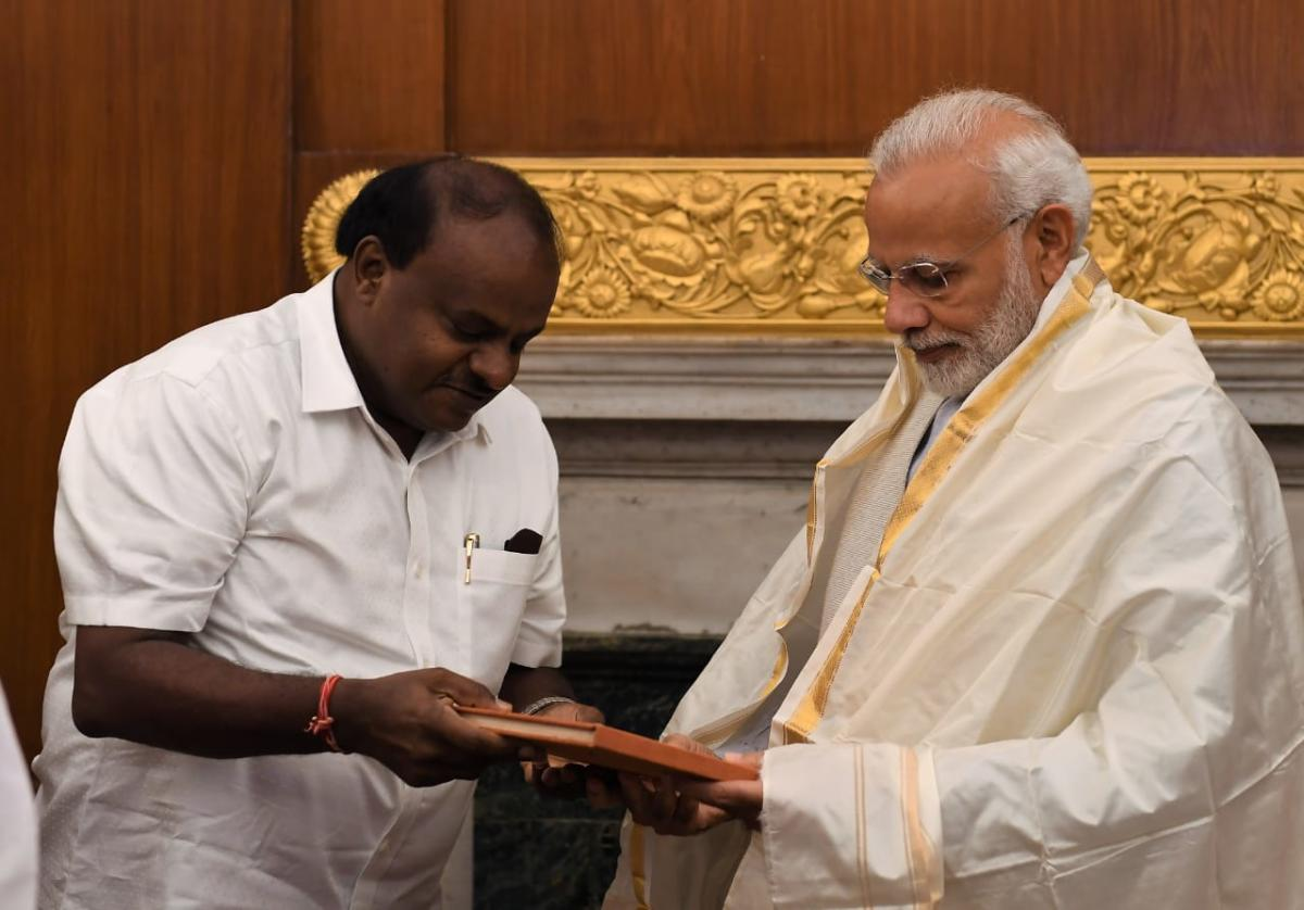 """Karnataka Chief Minister H D Kumaraswamy presents a book, """"The Open Eyes: A journey through Karnataka"""", written by renowned poet Dom Moraes, to Prime Minister Narendra Modi, in New Delhi on Monday. (Pic released by Press Information Bureau)"""