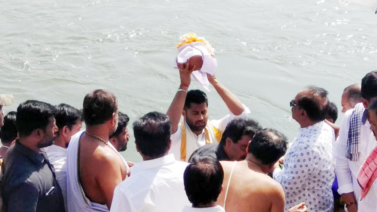 Abhishek Gowda, son of actor-politician M H Ambareesh, immerses the ashes of his father at Cauvery Sangama in Srirangapatna, Mandya district on Wednesday.