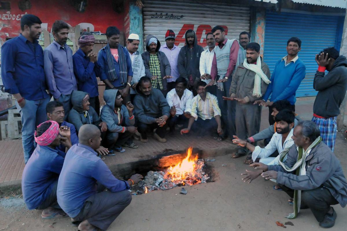 People lit a bonfire on the street to stay warm in the cold weather in Chikkamagaluru.