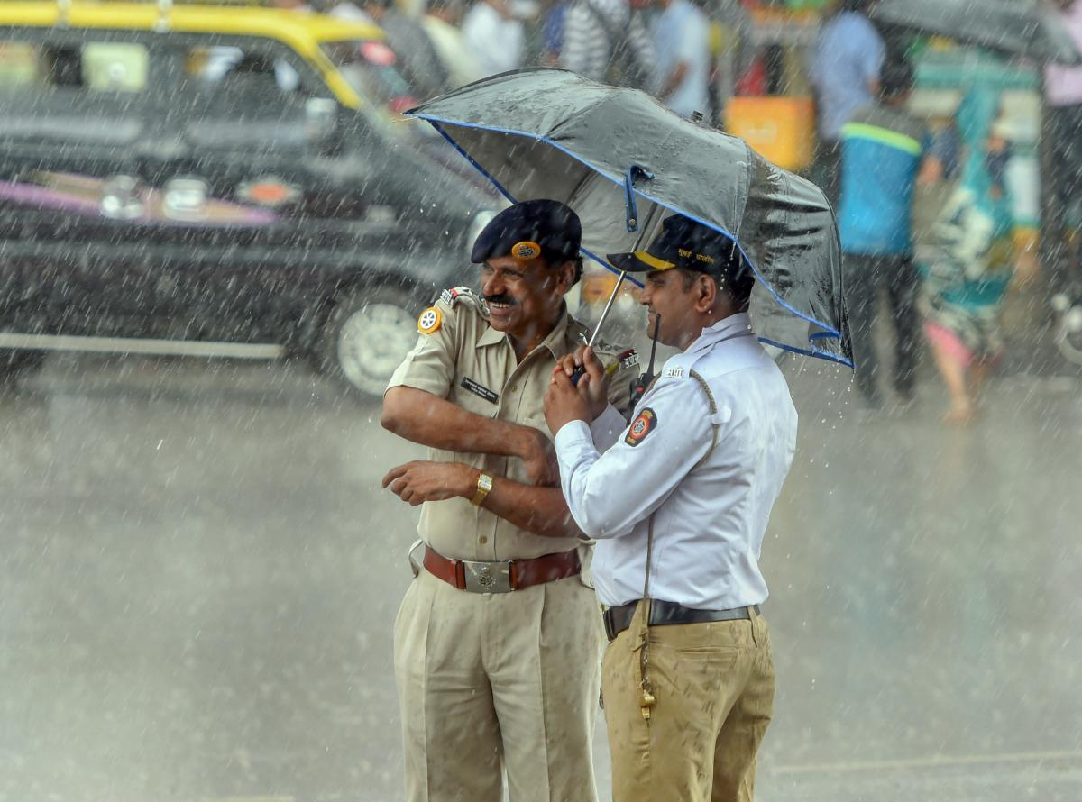 Police personnel take cover under an umbrella during Monsoon rains, in Mumbai. Reuters file photo for representation.