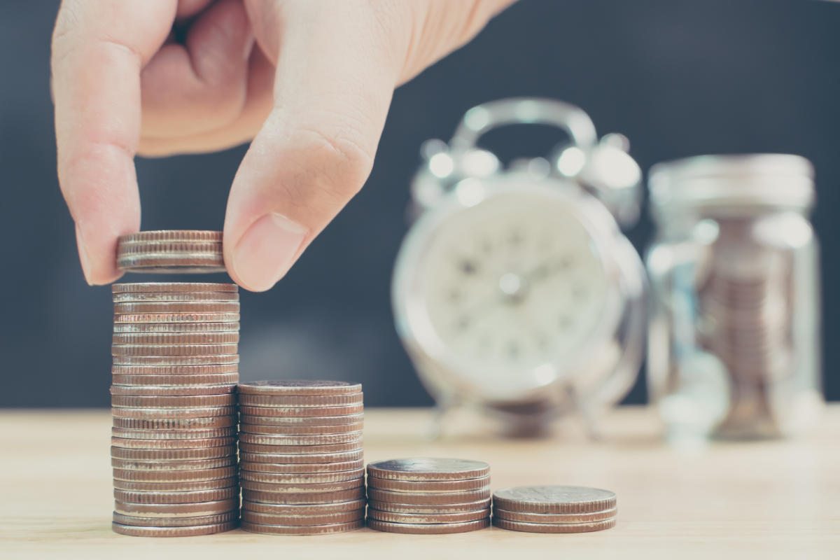 Hand of male or female putting coin stack step up increase save money with blurred clock and jar background, Finance and investment conceptMutual Funds