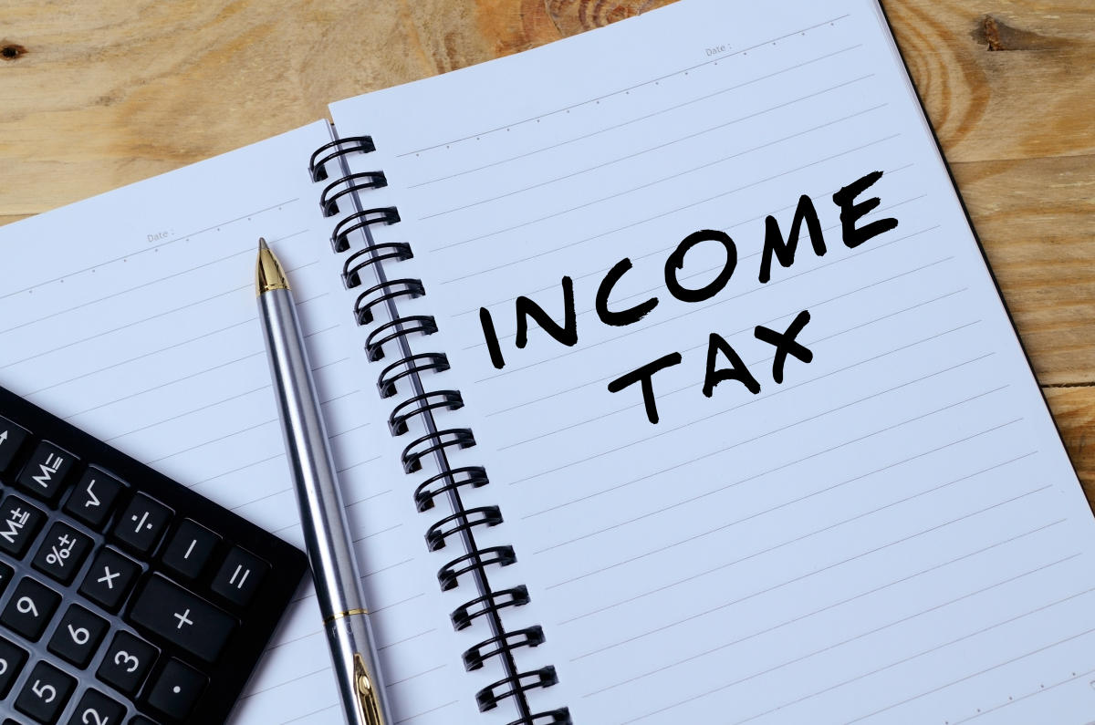 Notepad with pen and calculator.Income Tax