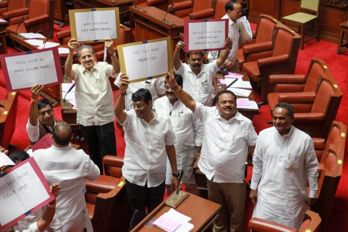 Congress and JD(S) MLCs protest against BJP in the Council in Vidhana Soudha, in Bengaluru on Monday. (DH Photo)