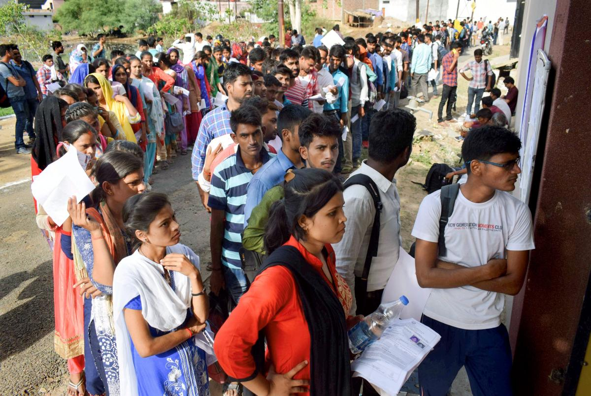 Applicants for Uttar Pradesh Police Constable Recruitment wait in a queue outside their exam centre, in Allahabad on Monday. (PTI Photo)