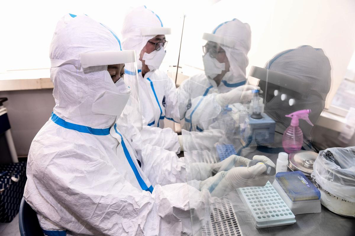 Laboratory technicians work on testing samples from people to be tested for the COVID-19 coronavirus at a laboratory in Shenyang in China's northeastern Liaoning province. (AFP Photo)