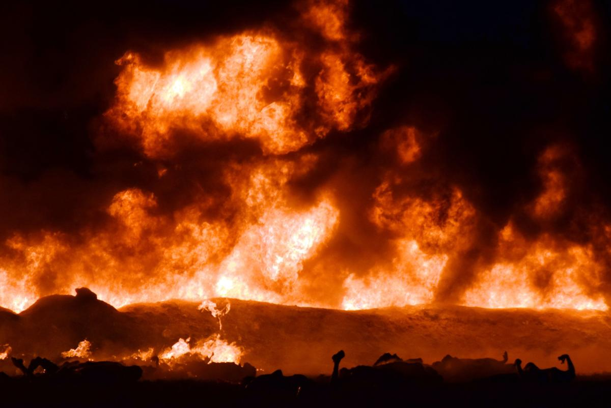 The fire is raging behind the bodies of burned victims at the scene of a massive blaze trigerred by a leaky pipeline in Tlahuelilpan, Hidalgo state, Mexico on January 18, 2019. - An explosion and fire has killed at least 66 people who were collecting fuel