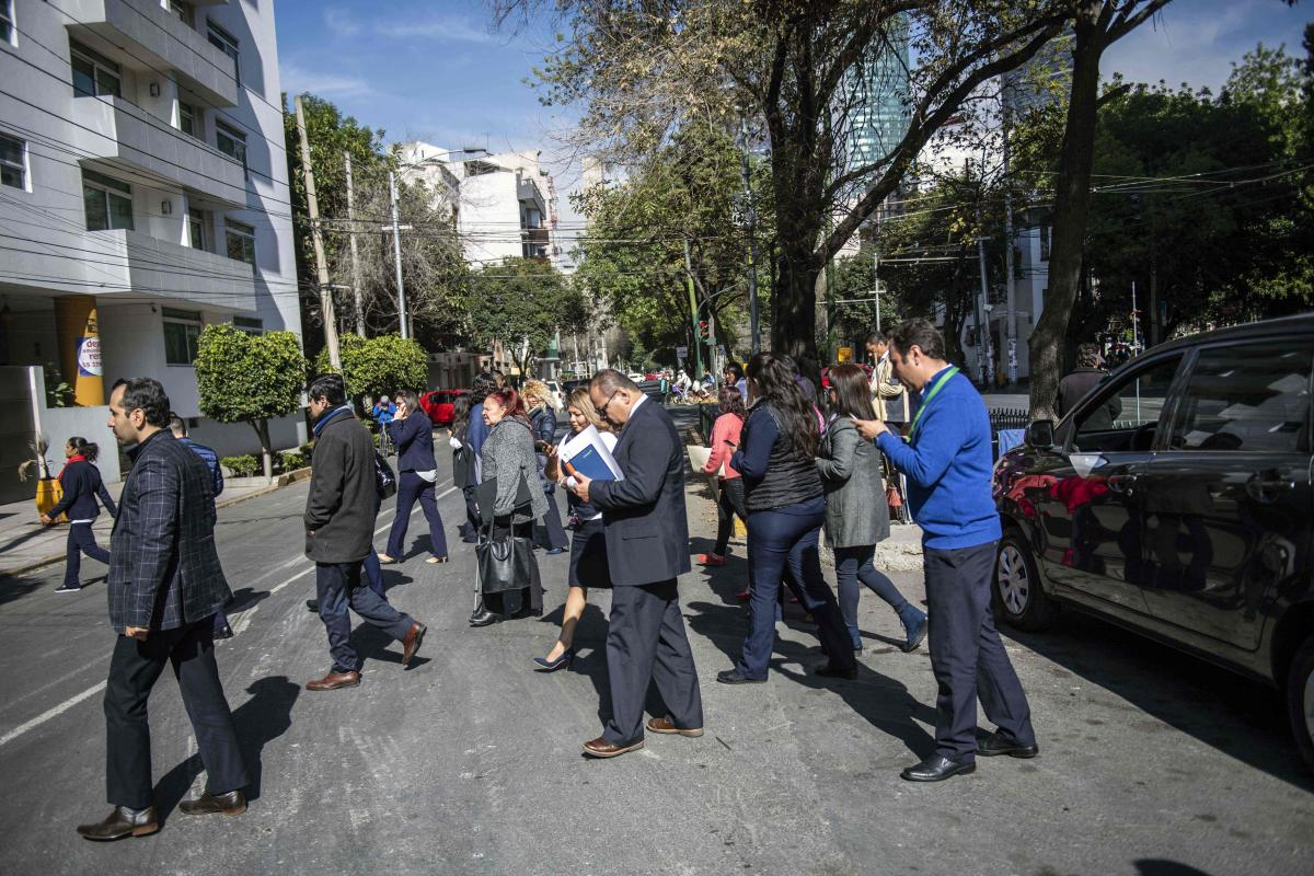 People wait on the streets after an earth tremor in Mexico City. AFP