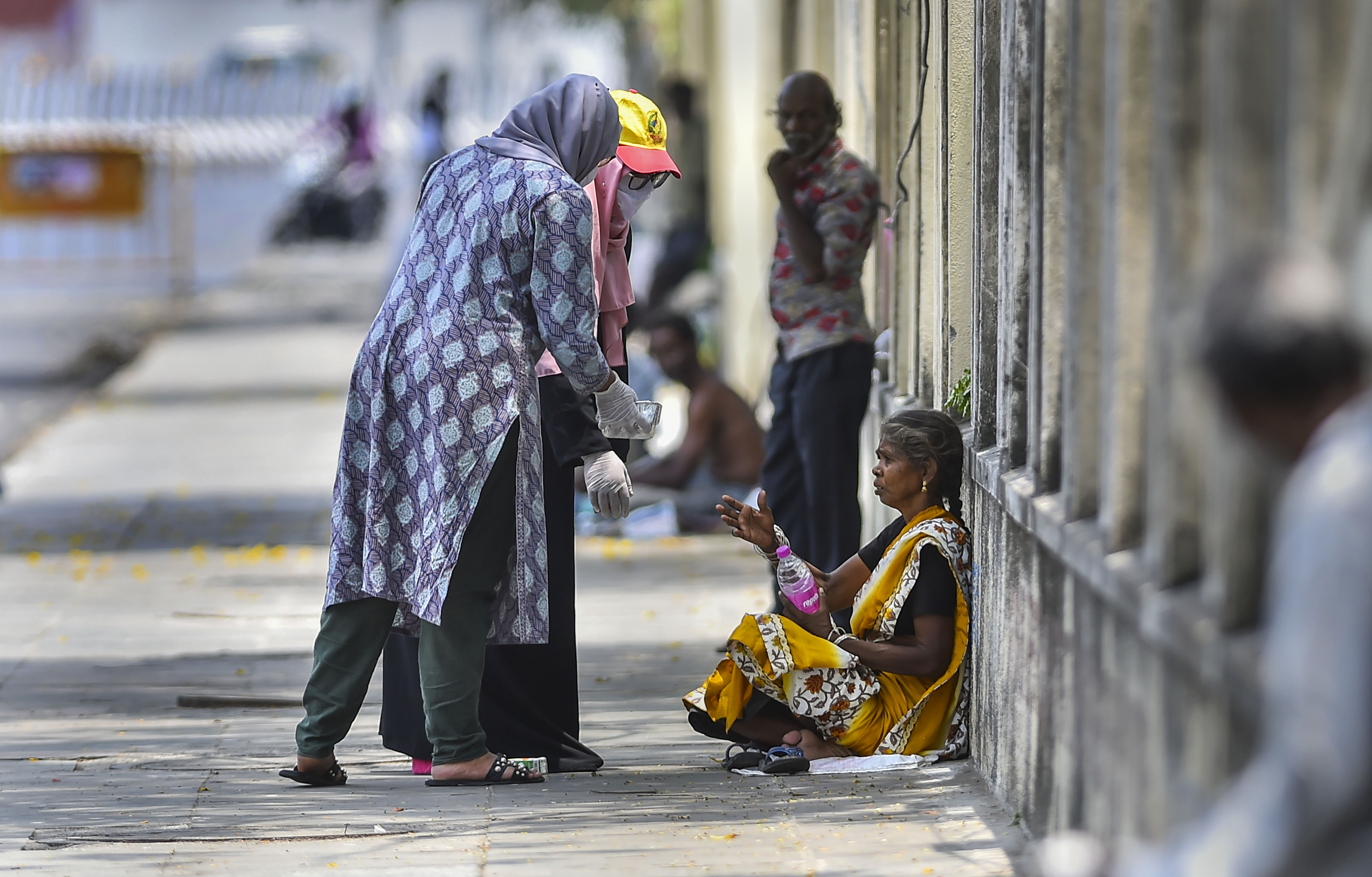 Two women offer food to a poor woman during the nationwide lockdown imposed to contain the spread of the COVID-19. (PTI Photo)