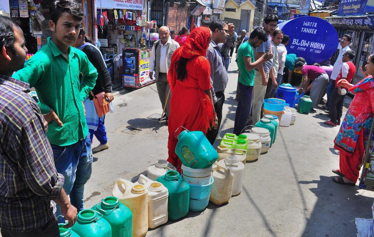 People stand in a queue to collect water from a tanker, as the city faces acute shortage of drinking water, in Shimla on Tuesday. PTI