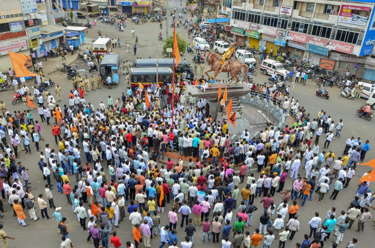 Maratha Kranti Morcha protesters block a road as police personnel keep a watch during their district bandh called for reservations in jobs and education, in Solapur, Maharashtra. PTI file photo