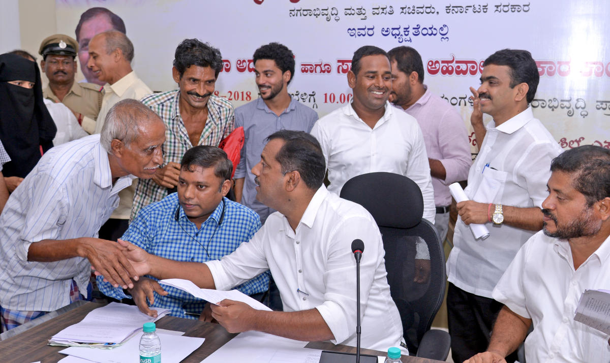 Minister for Urban Development and Housing U T Khader listens to grievances during a MUDA adalat in Mangaluru on Saturday.