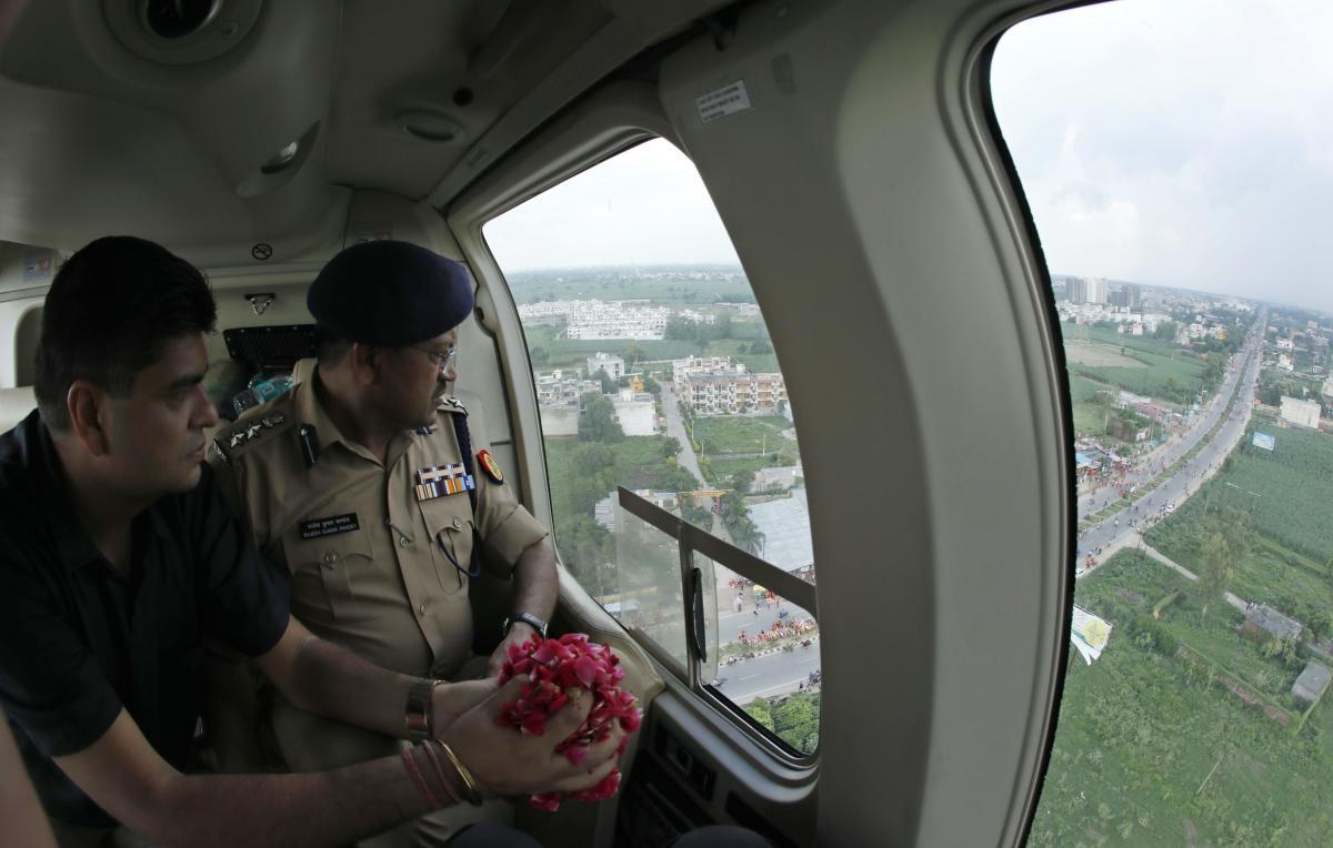 "Meerut District Magistrate Anil Dhingra (L) and Senior Superintendent of Police Rajesh Kumar Pandey (R) prepare to sprinkle rose petals over ""Kanwariyas"" during an aerial inspection, in Meerut on August 8, 2018. AFP"