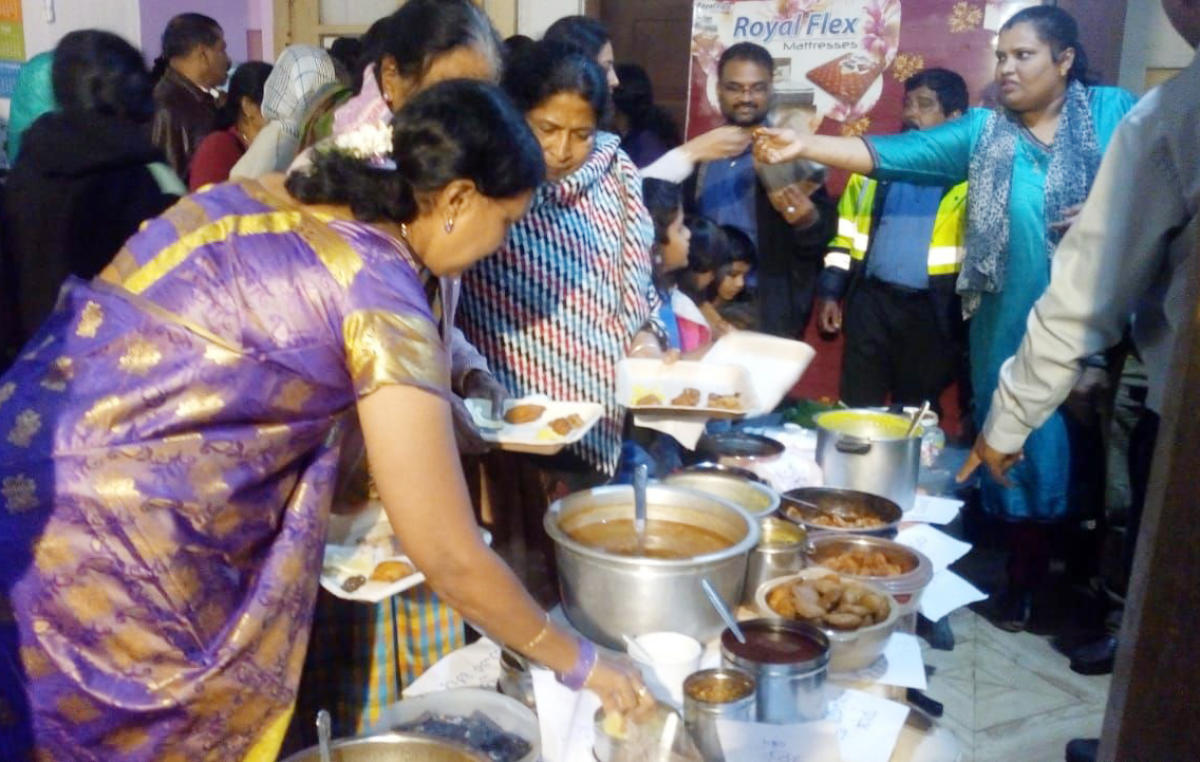 People relish traditional delicacies of Aati month, at the CSI Shanti Church premises in Madikeri on Sunday.