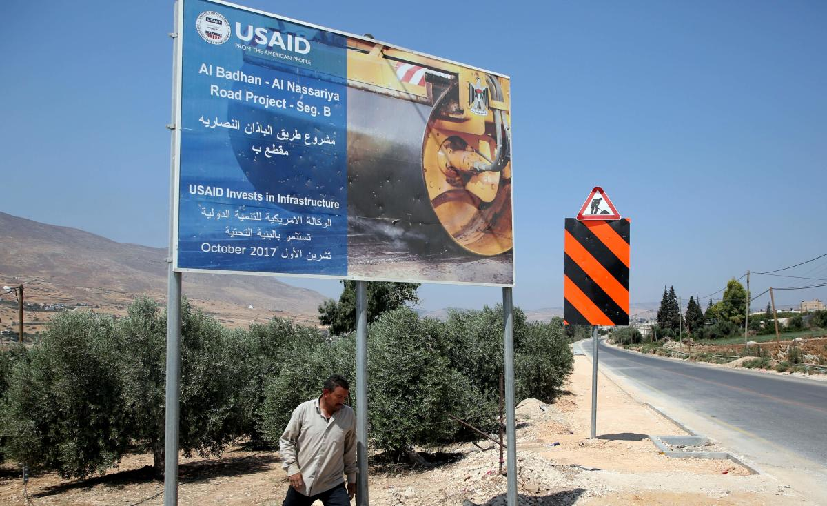 A Palestinian man walks near a USAID billboard in the village of al-Badhan, north of Nablus in the occupied West Bank on August 25, 2018. AFP