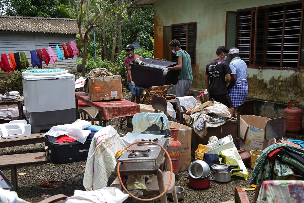 Volunteers collect household items in the lawns of a residential house before cleaning the house following floods in Kuttanad in Alappuzha district, Kerala. Reuters Photo
