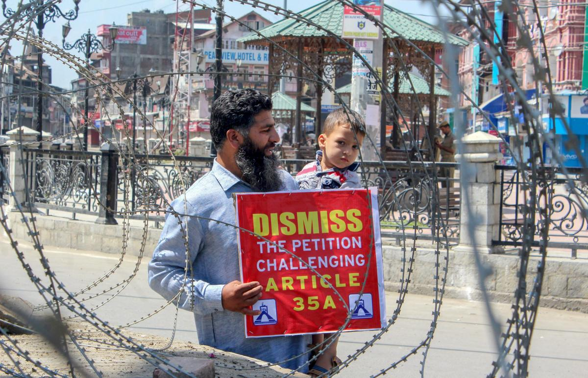 A man displays a placard during a protest march against the petitions challenging the validity of Article 35A, in Srinagar. PTI