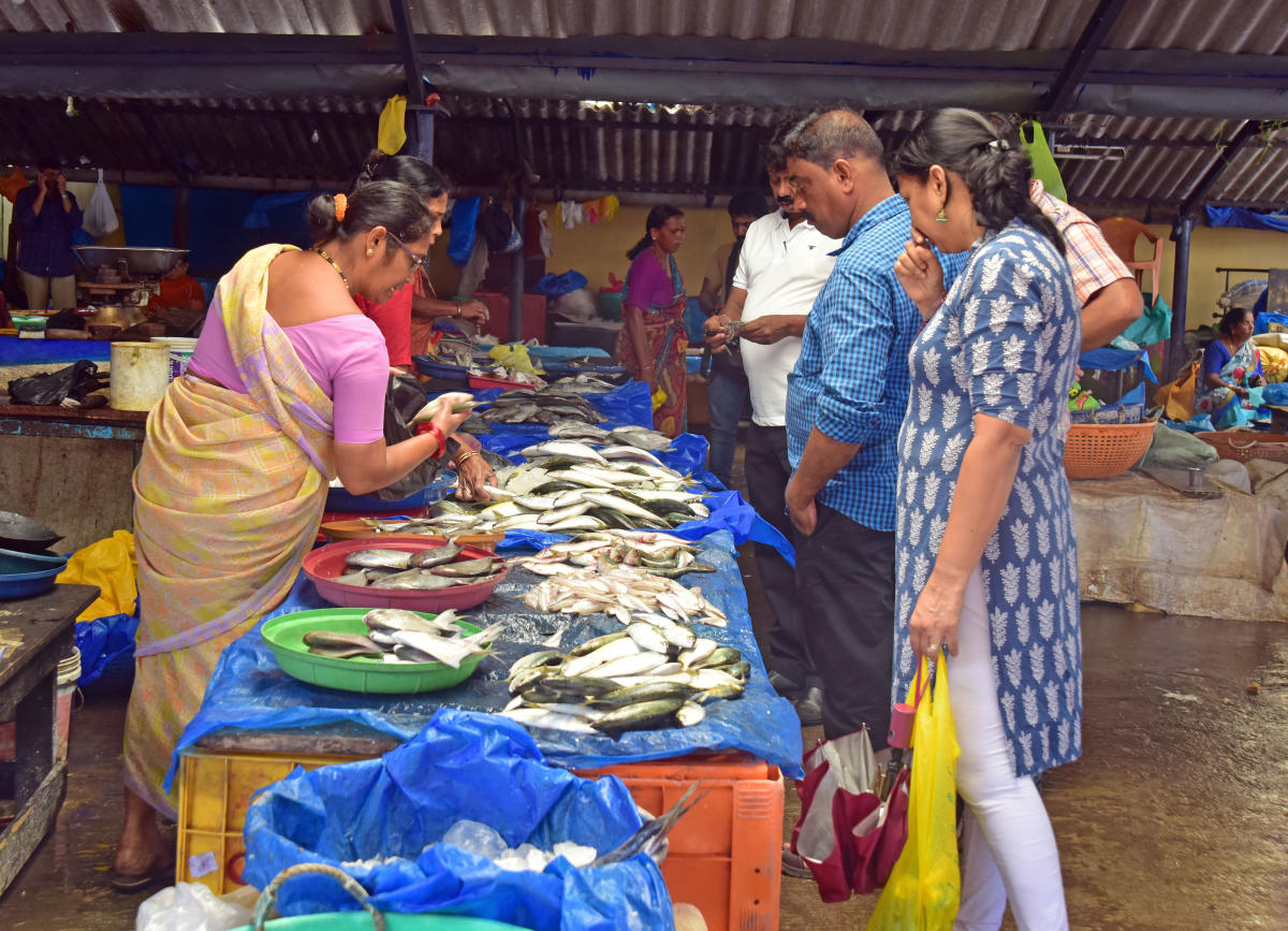 People buy fish at a market.