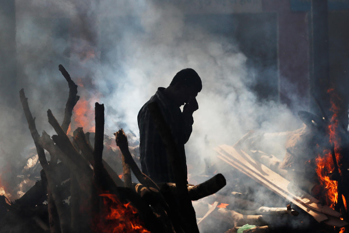 A man cries as he stands next to the burning pyre of a family member who died after a train traveling at high speed ran through a crowd of people on the rail tracks on Friday, at a cremation ground in Amritsar on Saturday. REUTERS