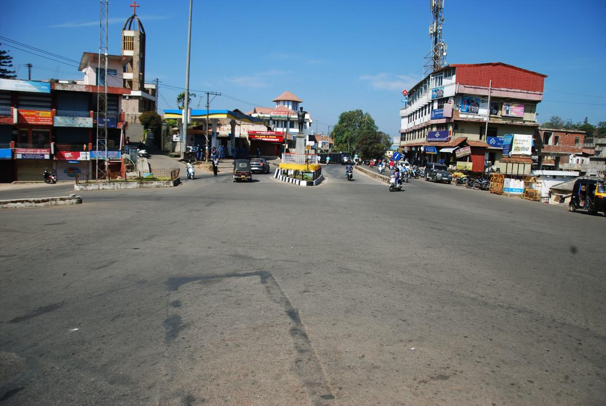 calm and the noise: Without private buses and autos, the busy General Thimmaiah Circle in Madikeri wore a deserted look on Saturday. (Right) Elected representatives from the BJP and Congress engage in arguments before the Tipu Jayanti in the town. dh phot