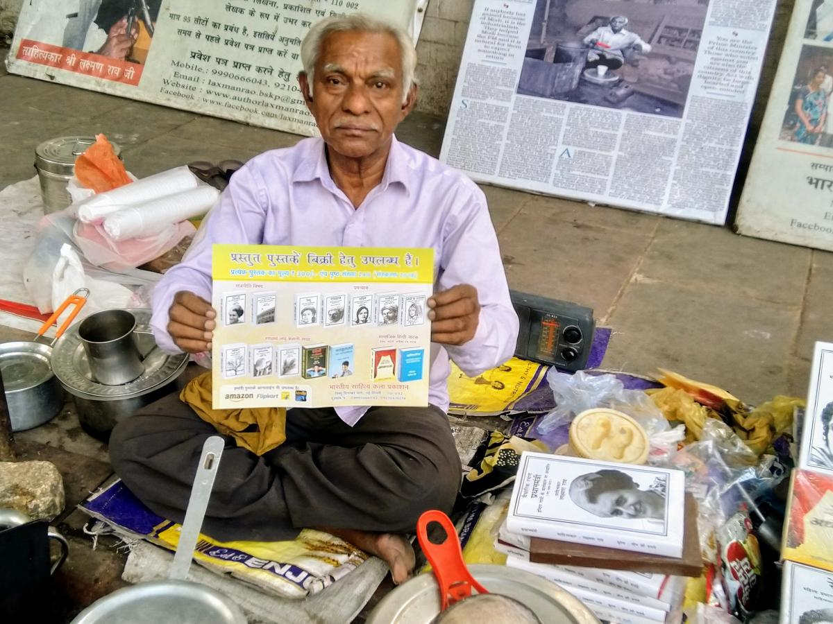 Words and vocation: Laxman Rao holds a self-published book at his tea stall in Delhi.