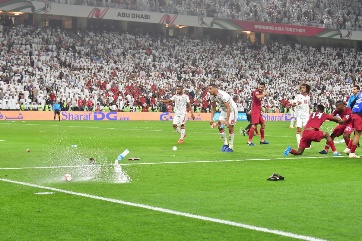 disgraceful Sandals and bottles are thrown at Qatar players as they celebrate a goal against UAE in the semifinal of the AFC Asian Cup in Abu Dhabi on Tuesday. Qatar defeated UAE 4-0 to set up a final clash against Japan. REUTERS