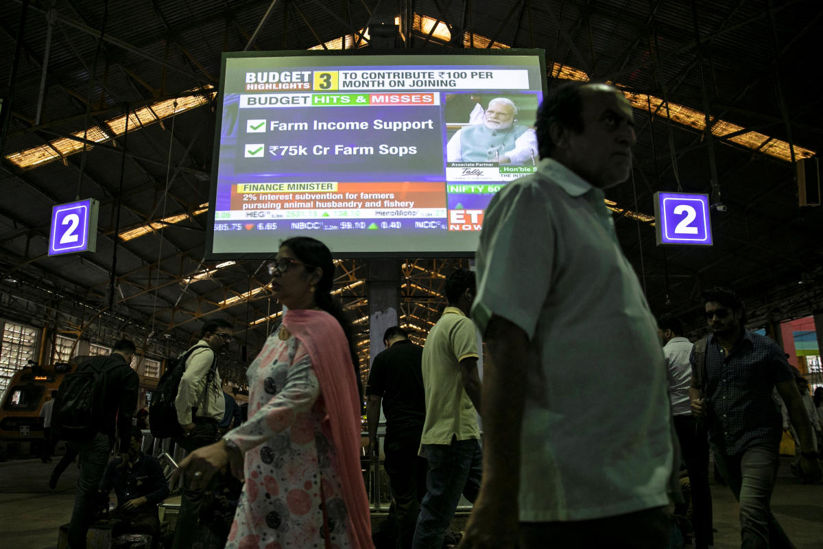 India's Prime Minister Narendra Modi is seen as commuters walk past a screen telecasting the interim budget speech at a railway station in Mumbai. (REUTERS)