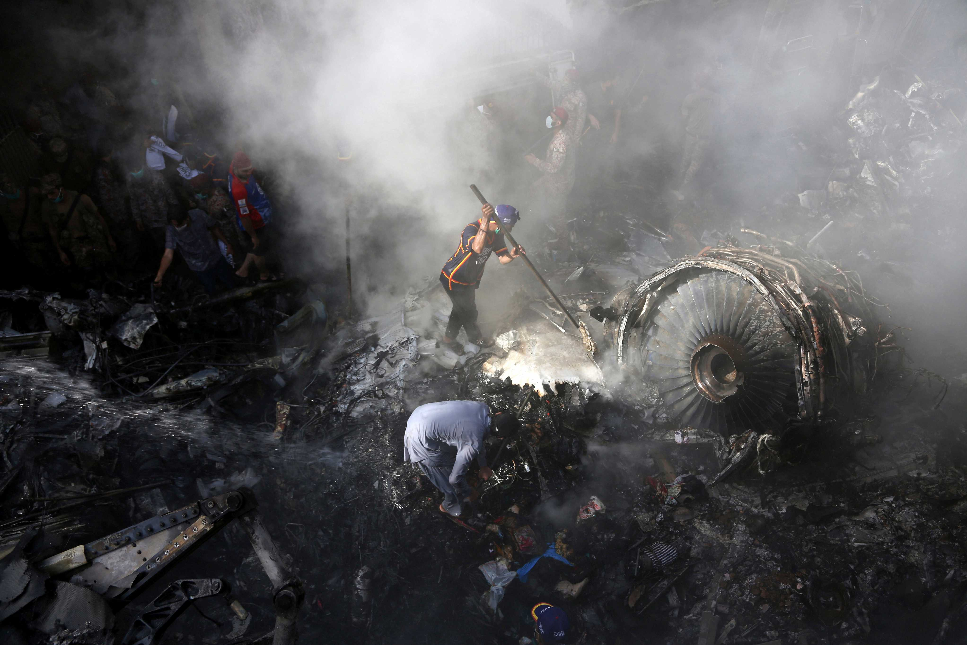 Volunteers look for survivors of a plane that crashed in a residential area of Karachi, Pakistan. (AP photo)