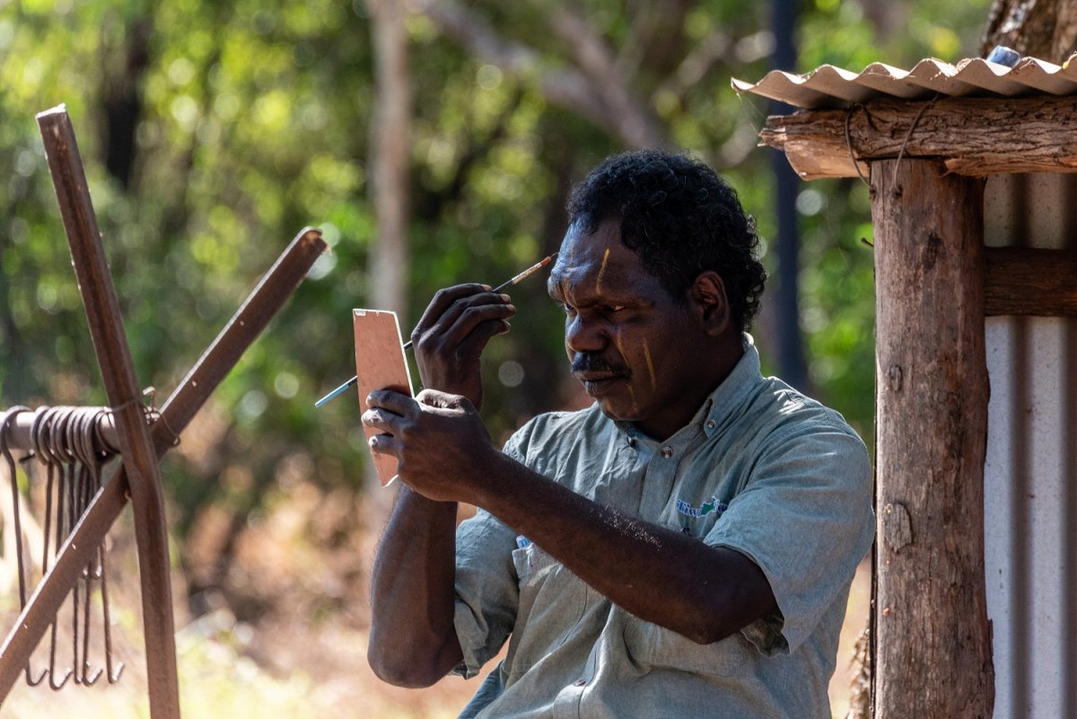 An aboriginal paints his face in Darwin