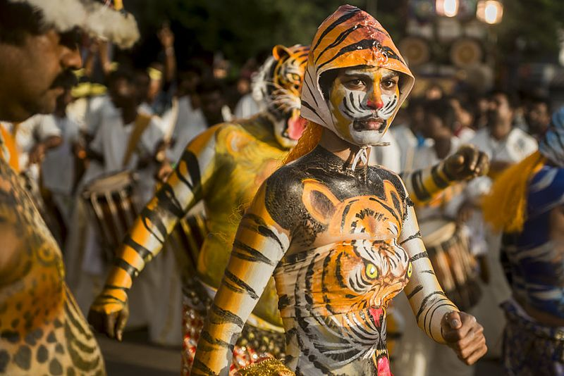 ulikali, is a celebration during Onam where people dress up, usually with tiger body painting and masks. Above is a woman (Rehana Fathima) with body art with her male colleagues celebrating the festival of Hinduism in the streets of Kerala. Wikicommons