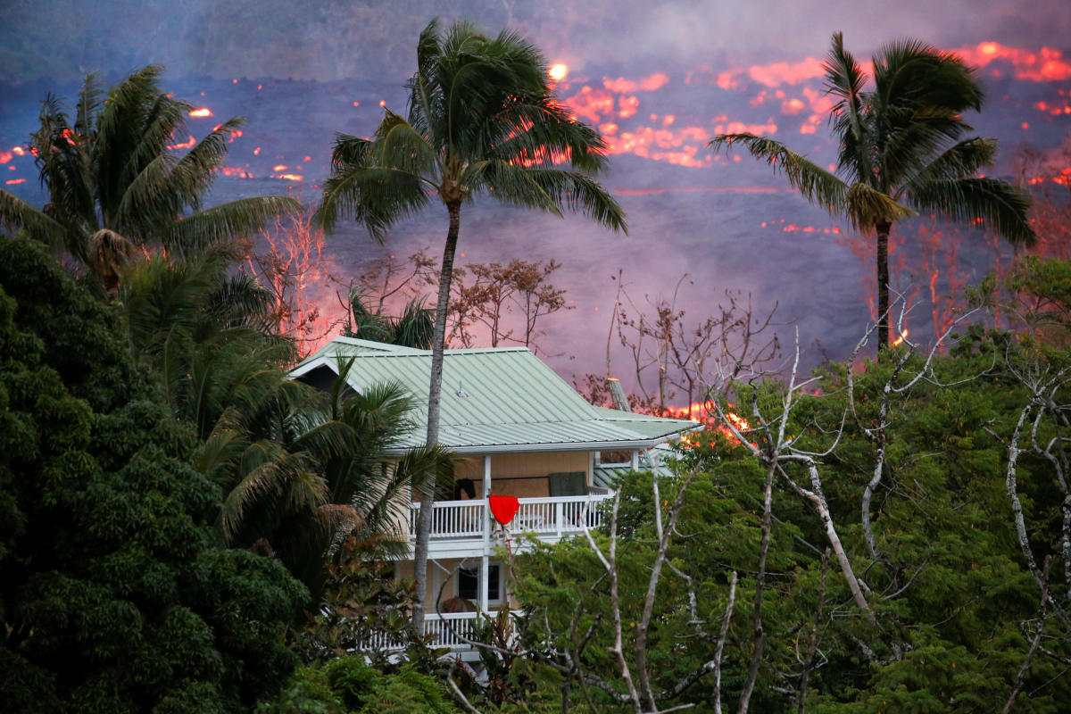 Lava flows near a house on the outskirts of Pahoa during ongoing eruptions of the Kilauea Volcano in Hawaii, U.S., May 19, 2018. REUTERS