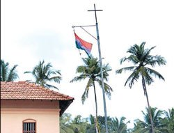 Flag hoisting on cross-topped pole leads to controversy