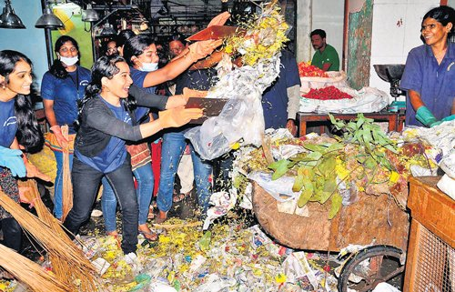 College students wield brooms  to rid KR Market of trash