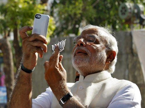Modi votes, clicks selfie, attacks Congress