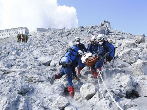 16 still missing on Japan volcano, typhoon threatens recovery