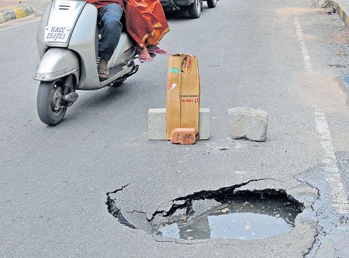 Road caves in, forms treacherous crater
