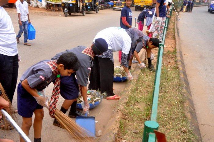 Volunteers clean bus stand, clear weeds, repair road