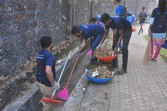 Volunteers clean drains, paint bus stop at Jeppu