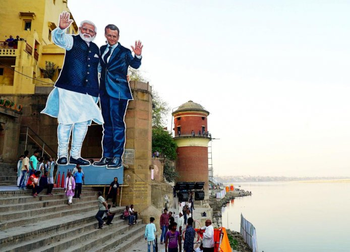 Banners used to hide Ganga filth during Macron ride