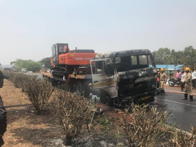 Truck carrying a JCB catches fire on national highway