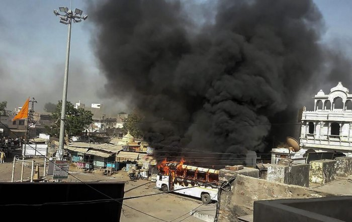 Smoke billows out of a burning bus during 'Bharat Bandh' call by Dalit organisations against the alleged dilution of Scheduled Castes/Scheduled Tribes Act, in Alwar. PTI