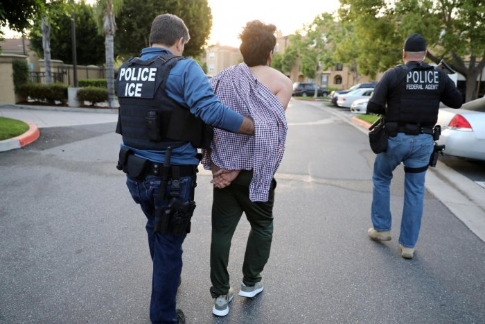 U.S. Immigration and Customs Enforcement (ICE) Assistant Field Office Director Jorge Field (L), 53, arrests an Iranian immigrant in San Clemente, California, U.S., May 11, 2017.