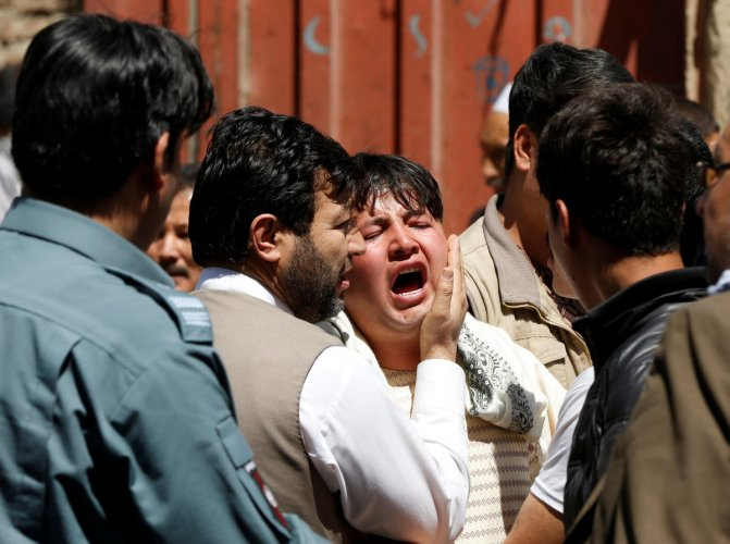 A man reacts as others comfort him at the site of a suicide attack in Kabul, Afghanistan April 22, 2018. REUTERS